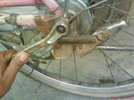 melepas mur pada as roda belakang dengan kunci pas/ring ukuran 14