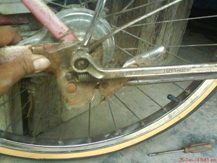 mengencangkan mur bersamaan sisi kanan dan sisi kiri as roda belakang