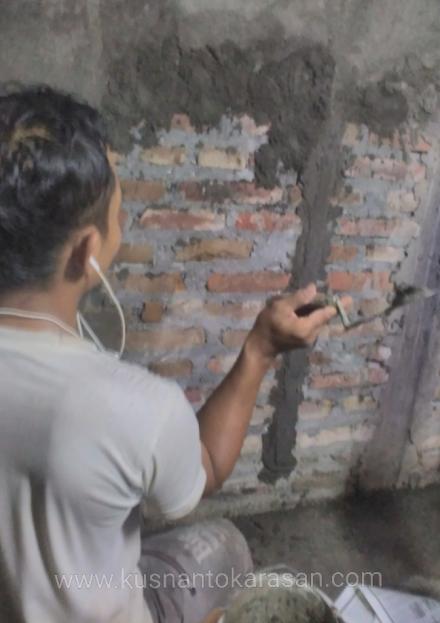 Disambitkan, satu cara menempelkan mortar ke tembok saat plester