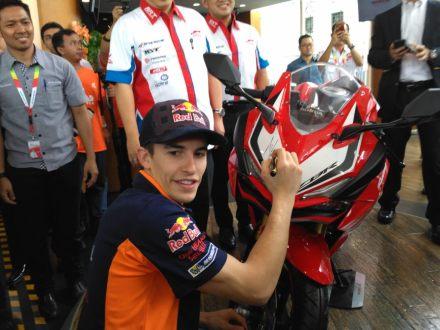 Marc Marquez membubuhkan tanda tangannya di front cover Honda CBR250RR