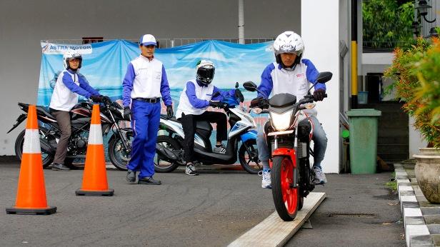 Salah seorang peserta pelatihan Safety Riding meniti papan keseimbangan (narrow plank) dalam sesi praktek. Materi yang diajarkan pada tahapan ini mendorong peserta untuk mampu menjaga keseimbangan saat berkendara dengan kecepatan rendah.